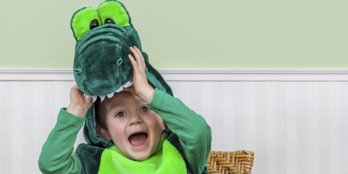 Adorable little boy in a crocodile suit