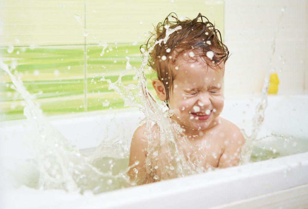 Dinosauriadas-niño pequeño salpicando agua en la bañera