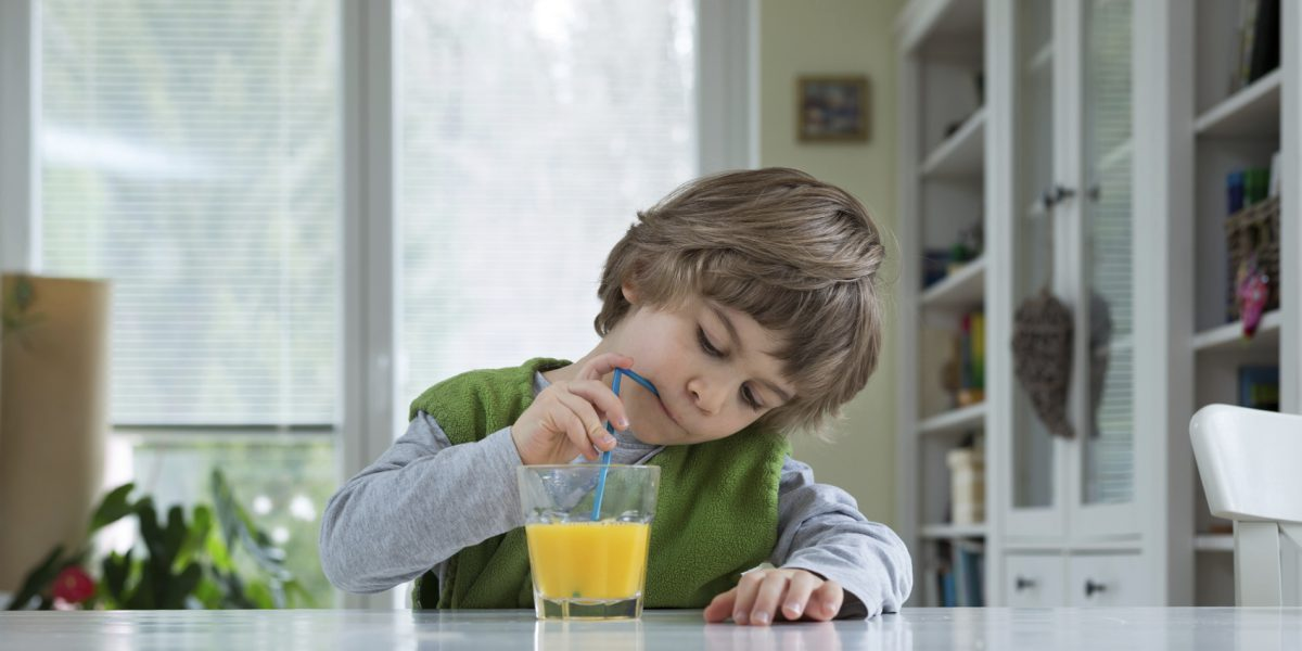 Cute little boy sitting at the table drinking orange juice for breakfast. Healthy lifestyle, nutrition and healthy eating